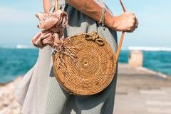有外面时兴的时髦的裸体藤条袋子和丝绸围巾的妇女手 巴厘岛,印度尼西亚热带海岛  藤条 免版税图库摄影