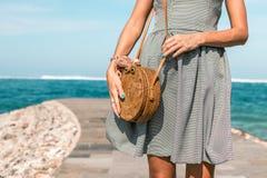 有外面时兴的时髦的裸体藤条袋子和丝绸围巾的妇女手 巴厘岛,印度尼西亚热带海岛  藤条 图库摄影