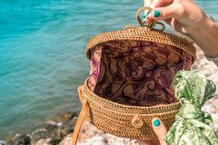 有外面时兴的时髦的裸体藤条袋子和丝绸围巾的妇女手 巴厘岛,印度尼西亚热带海岛  藤条 库存图片