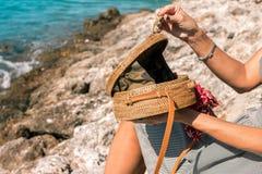 有外面时兴的时髦的裸体藤条袋子和丝绸围巾的妇女手 巴厘岛,印度尼西亚热带海岛  藤条 免版税库存照片