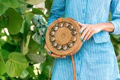 有外面时兴的时髦的裸体藤条袋子和丝绸围巾的妇女手 巴厘岛,印度尼西亚热带海岛  藤条 免版税库存图片