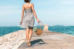 有外面时兴的时髦的裸体藤条袋子和丝绸围巾的妇女 巴厘岛,印度尼西亚热带海岛  藤条 免版税库存图片