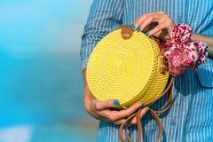 有外面时兴的时髦的黄色藤条袋子和丝绸围巾的妇女手 巴厘岛,印度尼西亚热带海岛  免版税库存照片