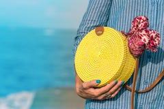 有外面时兴的时髦的黄色藤条袋子和丝绸围巾的妇女手 巴厘岛,印度尼西亚热带海岛  免版税库存图片