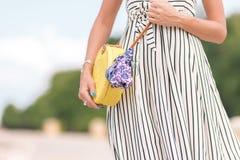 有外面时兴的时髦的黄色藤条袋子和丝绸围巾的妇女 巴厘岛,印度尼西亚热带海岛  藤条 免版税库存图片