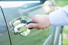 有外面汽车钥匙的人,插入关键门户开放主义的汽车(被聚焦的手指) 免版税图库摄影