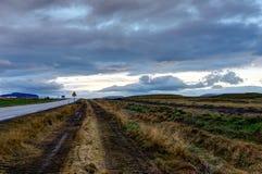 有多云天空和冰岛风景的空的街道在Sunr期间 免版税图库摄影