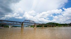 有多云天空和棕色河的一座桥梁 免版税库存照片