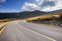 有多云天空和阳光的空的柏油路在山和 库存图片