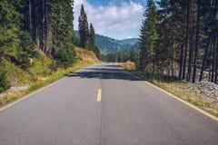 有多云天空和阳光的空的柏油路在山和 免版税图库摄影