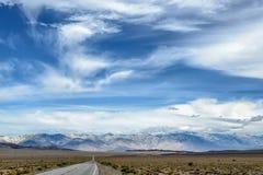 有多云天空和阳光的空的柏油路 免版税库存照片