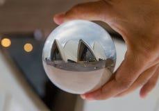 有多云天空摄影的歌剧院在清楚的水晶玻璃球 免版税库存图片