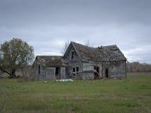 有多云天空的惨淡的被放弃的被毁坏的农厂议院 库存图片