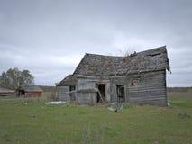 有多云天空的惨淡的被放弃的被毁坏的农厂议院 免版税库存图片