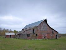 有多云天空的惨淡的被放弃的被毁坏的农厂谷仓 免版税库存照片