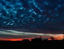 有多云日落的现出轮廓的农场 库存照片