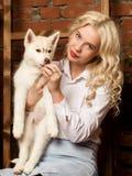 有多壳的小狗的愉快的白肤金发的妇女在秋天收获背景 免版税库存照片