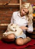 有多壳的小狗的愉快的白肤金发的妇女在秋天收获背景 库存图片