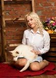 有多壳的小狗的愉快的白肤金发的妇女在秋天收获背景 免版税图库摄影