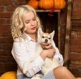 有多壳的小狗的愉快的白肤金发的妇女在秋天收获背景 库存照片