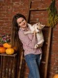 有多壳的小狗的愉快的美丽的妇女与在砖墙背景的秋天收获 免版税库存图片