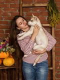 有多壳的小狗的愉快的美丽的妇女与在砖墙背景的秋天收获 库存图片