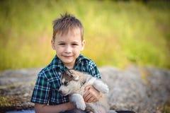 有多壳的小狗的男孩 库存图片