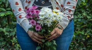 有多彩多姿的花的女孩在她的手上 库存照片