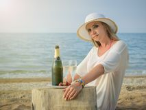 有多彩多姿的镯子的妇女在她的有一个瓶的胳膊由海的香槟 库存图片