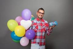有多彩多姿的baloons的英俊的行家人在演播室 免版税库存照片