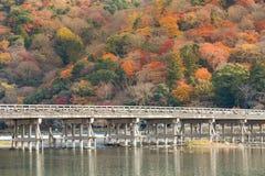 有多棵颜色树的Togetsukyo桥梁在山背景 免版税库存照片