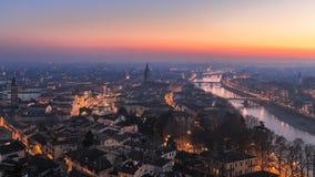 有夜城市照明的维罗纳和有用平衡的薄雾盖的桥梁的阿迪杰河城市的全景 免版税图库摄影