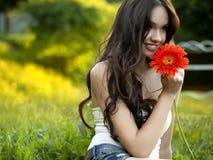 有大丁草花的美丽的女孩 图库摄影