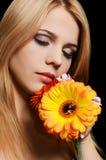 有一朵大丁草花的美丽的妇女在黑背景 库存图片