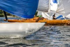 有大三角帆的经典航行游艇在赛船会的一个湖 免版税库存图片