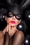 有大乳房的性感的妇女,佩带一只黑面具复活节兔子 免版税库存图片