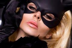 有大乳房的性感的妇女,佩带一只黑面具复活节兔子 库存照片