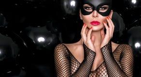 有大乳房的性感的妇女,佩带一只黑面具复活节兔子 免版税图库摄影
