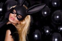 有大乳房的性感的妇女,佩带一只黑面具复活节兔子 图库摄影