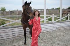 有大乳房的美丽和性感的金发碧眼的女人在一件红色礼服和棕色衣服马  图库摄影