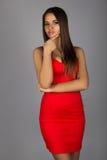 有大乳房的魅力浅黑肤色的男人在性感的红色礼服 免版税库存图片