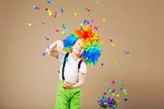 有大五颜六色的假发的愉快的小丑男孩 让` s党!滑稽的孩子 库存照片