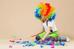 有大五颜六色的假发的愉快的小丑男孩 让` s党!滑稽的孩子 免版税库存照片