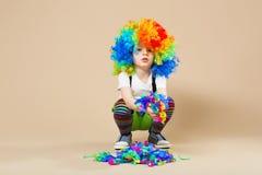 有大五颜六色的假发的愉快的小丑男孩 让` s党!滑稽的孩子 免版税图库摄影
