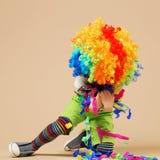 有大五颜六色的假发的愉快的小丑男孩 图库摄影