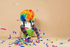 有大五颜六色的假发的愉快的小丑男孩 免版税库存照片