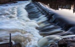 有大厦的急流和反射的一条起泡的河在早期的春天 库存图片