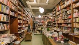有大和明亮的书店的书和顾客的书架 免版税库存图片