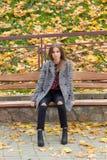 有大哀伤的眼睛的美丽的甜女孩在外套坐在秋天的长凳在下落的黄色中留给秋天明亮 免版税图库摄影