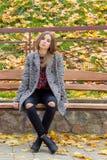 有大哀伤的眼睛的美丽的甜女孩在外套坐在秋天的长凳在下落的黄色中留给秋天明亮 免版税库存图片